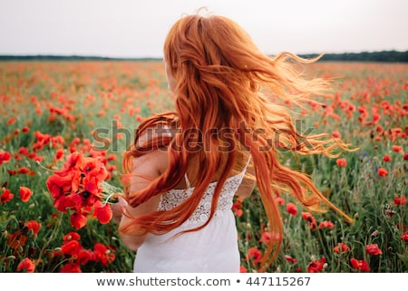 happy red haired girl with flowers Stock photo © dolgachov