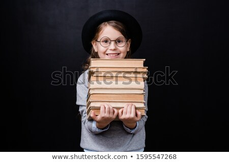 Cheerful schoolgirl with toothy smile holding stack of books in isolation Stock photo © pressmaster