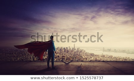 man in red superhero cape over sunset in city Stock photo © dolgachov