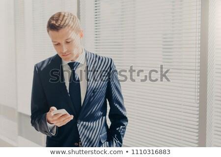 Başarılı genç pahalı takım elbise cep telefonu Stok fotoğraf © vkstudio