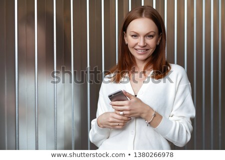 Positive young woman with appealing look, has satisfied facial expression, dressed in white clothes, Stock photo © vkstudio