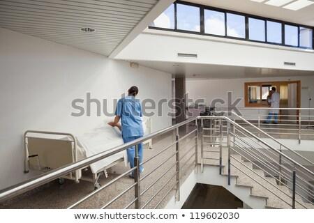 Nurse tending to patient in bed in hospital corridor Stock photo © wavebreak_media