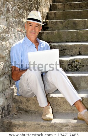 senior ma n relaxing outdoors with his laptop stock photo © photography33