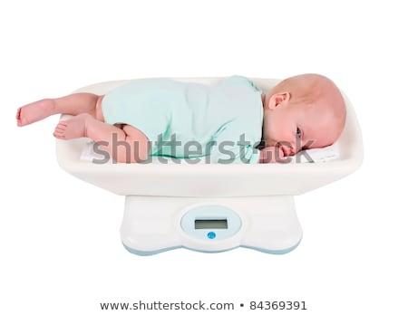 baby girl on on weighing scale Stock photo © balasoiu