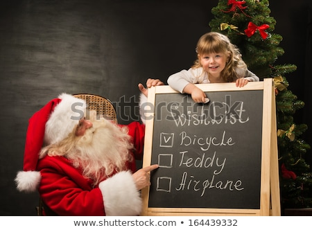 Santa Claus with child sitting near chalkboard with wish list an Stock photo © HASLOO