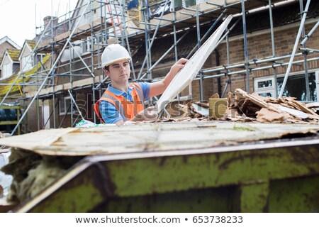 Zdjęcia stock: Builder Putting Waste Into Rubbish Skip