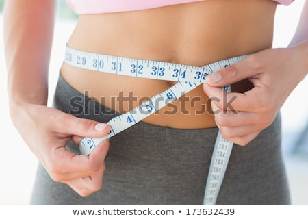 Close-up mid section of a woman measuring waist Stock photo © wavebreak_media