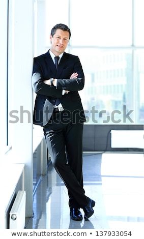 Happy young business man leaning on a wall Stock photo © feedough