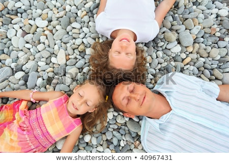 Happy family with little girl lying on stony beach, closed eyes, stock photo © Paha_L