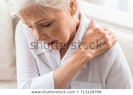 Vrouw lijden schouderpijn triest jonge vrouw witte Stockfoto © AndreyPopov