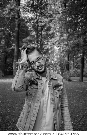 man wearing glasses while fixing his jacket stock photo © feedough