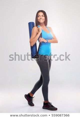 Cheerful beautiful fitness woman holding yoga mat and looking away Stock photo © deandrobot