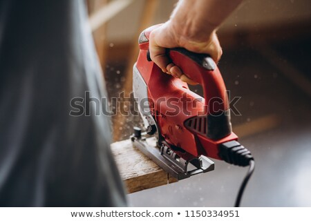 Carpenter woman cutting board with jig saw Stock photo © Kzenon