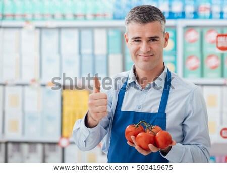 Supermarket clerk holding tomatoes Stock photo © stokkete