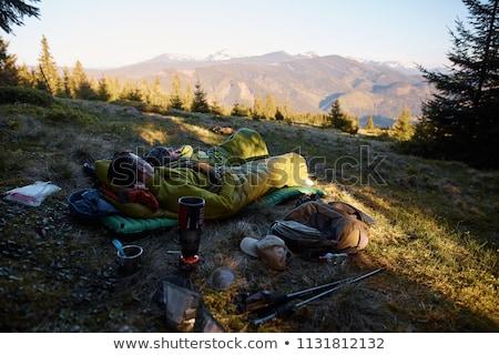 man resting in sleeping bag in the mountains stock photo © rastudio