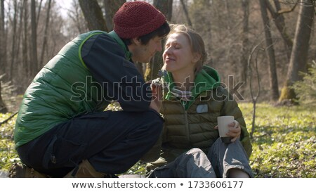 Husband giving wife flowers outdoors kissing and smiling Stock photo © monkey_business
