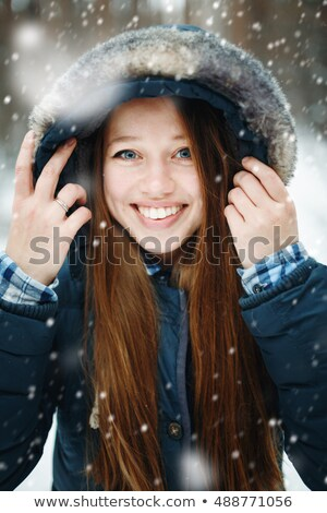 Headshot of young woman standing under snowfall Stock photo © dariazu