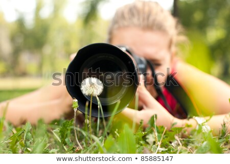 Woman taking photograph by flowers Stock photo © IS2