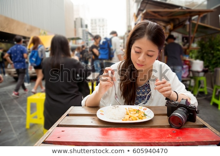 Stock photo: Asian woman outdoors. Girleating street food during lunch