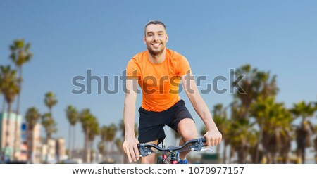 happy young man riding bicycle over venice beach Stock photo © dolgachov