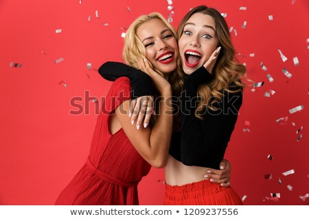happy young friends women standing isolated over red background over konfetti stock photo © deandrobot