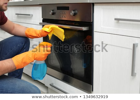 Zdjęcia stock: Man With Rag Cleaning Oven Door At Home Kitchen