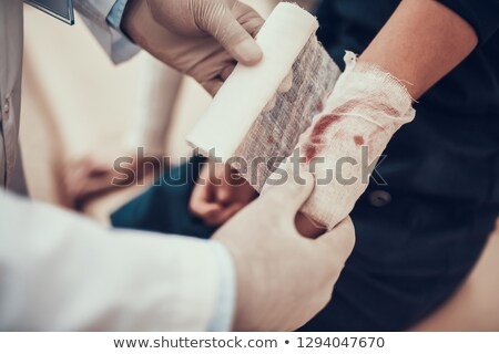 Doctor Tying Bandage On Patient's Hand Stock photo © AndreyPopov