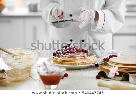Woman confectioner making raspberry cake Stock photo © Kzenon