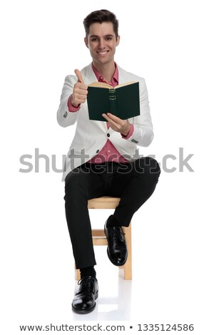seated  man reading a book and makes the ok sign Stock photo © feedough