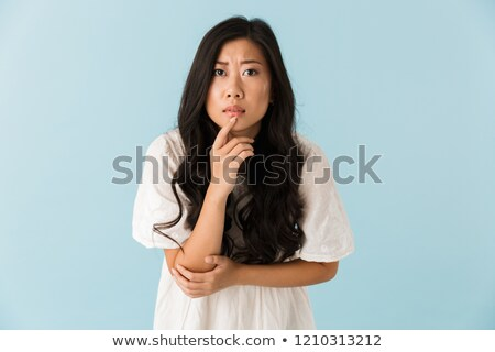 Thinking scared young asian beautiful woman posing isolated over blue background. Stock photo © deandrobot