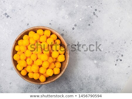 Puffed golden cheese balls as classic kids snack on light background. Stock photo © DenisMArt