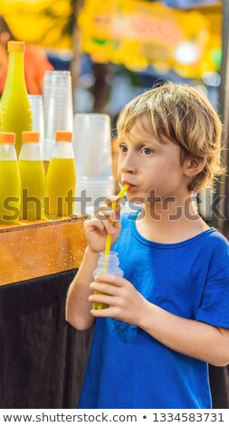 Boy drinking sugar cane juice on the Asian market VERTICAL FORMAT for Instagram mobile story or stor Stock photo © galitskaya