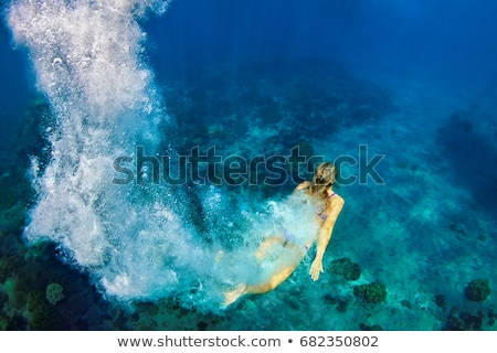 Happy young woman swimming underwater in the tropical ocean Stock photo © galitskaya