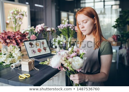 Busy attractive girl in apron standing by counter Stock photo © pressmaster