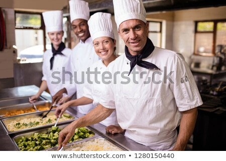 Group of chefs stirring prepard foods in kitchen at hotel Stock photo © wavebreak_media