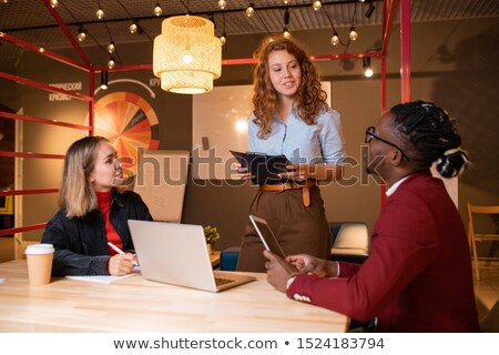 Two young intercultural managers listening to report of successful colleague Stock photo © pressmaster