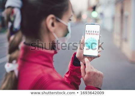 Woman using a phone with the coronavirus tracking app installed Stock photo © Kzenon