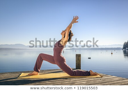 Woman doing yoga on jetty Stock photo © photography33