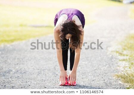 Fit woman bending over and touching her toes Stock photo © stockyimages