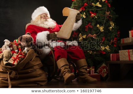 santa claus sitting in armchair near christmas tree at home and stock photo © hasloo