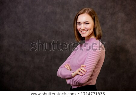 Businesswoman standing with arms crossed pointing sideways stock photo © bmonteny