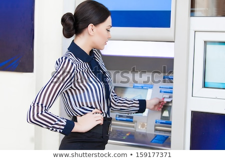 Smiling Woman Inserting a Card in an ATM Stock photo © stryjek