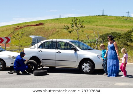 Woman tyre change car break down remote road Stock photo © roboriginal