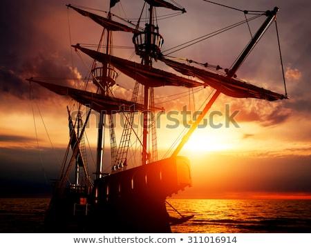 Pirate ship on peaceful ocean at sunset. Stock photo © maxmitzu