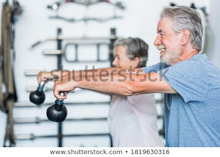 Woman and men having fun doing fitness sport in gym Stock photo © Kzenon