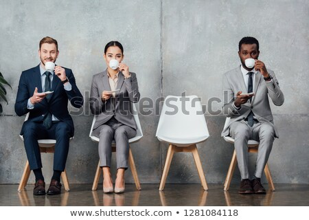 Attractive african businessman drinking coffee. Coworking. Stock photo © deandrobot