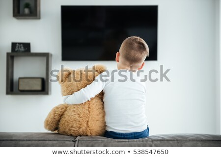 Boy sitting on sofa with teddy bear and watching TV stock photo © deandrobot