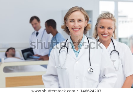 Two doctors, smiling, in front of x-rays Stock photo © IS2