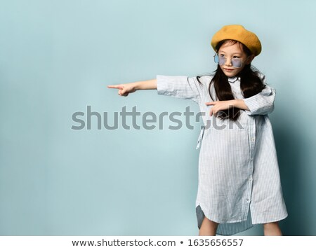 Little asian schoolgirl pointing forefinger up. Stock photo © RAStudio