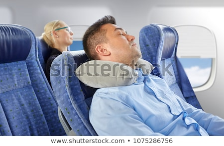 man sleeping in plane with cervical neck pillow Stock photo © dolgachov
